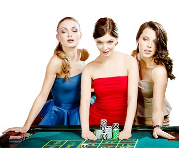 Three attractive girls, dressed well, playing the game of roulette and having fun.