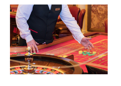 Male live roulette dealer presenting the red felt table.